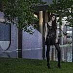 Young fashion model outdoor shoot posing wearing short black dress — Stock Photo #26690309
