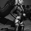 A young blond sexy lady mistress with bright red lips wearing a black leather costume laying in a bed — Photo