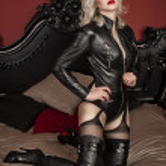 une maîtresse de la jeune dame sexy blonde avec des lèvres rouges vives vêtu d'un costume de cuir noir pose dans un lit — Photo #26849655