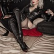 A young blond sexy lady mistress with bright red lips wearing a black leather costume laying in a bed — Stock Photo