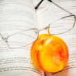 Nectarine and reading glasses — Stock Photo