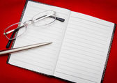 Reading glasses on notepad — Stock Photo