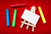 Coloured pens beside easel — Stock Photo