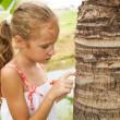 Sad little girl near a tree — Stock Photo #12691832