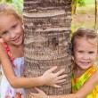 Two happy sisters near a tree — Stock Photo
