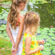 Stock Photo: Two girls standing near pond