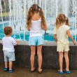 Two girls and a little boy standing near the fountain back to the camera — Stock Photo