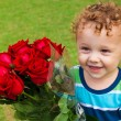 Stock Photo: Happy child with a bouquet of red roses