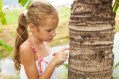 Sad little girl near a tree — Stock Photo