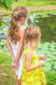 Two girls standing near pond — Stock Photo