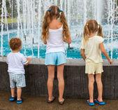 Duas meninas e um menino de pé junto à fonte de volta para a câmera — Fotografia Stock