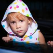 Sad little girl sitting in the car near the window — Stock Photo #12739130