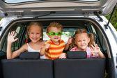 Tres niños felices en el coche — Foto de Stock