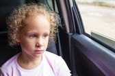 Sad little girl sitting in the car near the window — Stockfoto