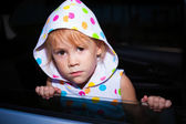 Sad little girl sitting in the car near the window — Stok fotoğraf