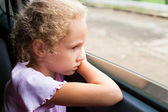 Sad little girl sitting in the car near the window — Стоковое фото
