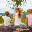 Happy children sitting on a bench near the tree — Stock Photo