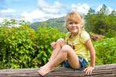 Happy child sits on a log in the background of mountains — Stock Photo
