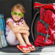 Little girl sitting in the car with backpacks — Stock Photo #14178297