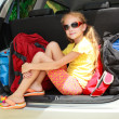 Little girl  sitting in the car with backpacks - Foto Stock