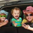 Three happy kids in the car — Stockfoto