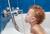 Cute one year old boy taking a relaxing bath with foam. — Stock Photo