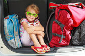 Little girl sitting in the car with backpacks — Stock Photo