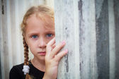 Sad little girl on the background of an wall — Stock Photo