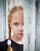 Sad little girl on background the wall — Stock Photo