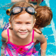 Happy little girl splashing around in the pool — Stock Photo