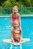 Zwei glückliche kleine Mädchen im Pool planschen — Stockfoto