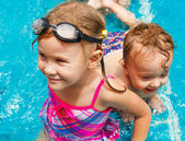 Little girl and little boy playing in the pool — Stock Photo