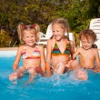 Stock Photo: Two little girls and little boy playing in the pool