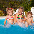 Two little girls and little boy playing in the pool — Stock Photo #22348255