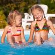 Two little girls playing in the pool — Stock Photo #22348367