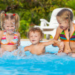 Two little girls and little boy playing in the pool — Stock Photo #22348423