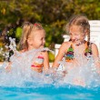 Two happy little girls splashing around in the pool — Stock Photo #22348473