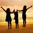 Three kids silhouettes standing on beach at sunset — Stock Photo #22349775