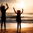 Two happy girls jumping on the beach on the dawn time — Stock Photo