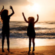Two happy girls jumping on the beach on the dawn time — Stockfoto