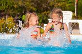 Two happy little girls splashing around in the pool — Stock Photo