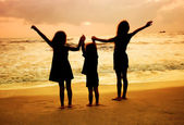 Three kids silhouettes standing on beach at sunset — Stockfoto