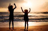 Två glada tjejer som hoppar på stranden på dawn tiden — Stockfoto