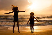Happy girls jumping on the beach on the dawn time — Foto Stock