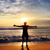 Man with his hands up on the dawn on the beach — Stock Photo