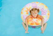 The little girl in the swimming pool with rubber ring — Stock Photo