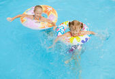 Two happy little girls splashing around in the pool — Stock Photo