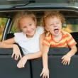 Two happy kids in the car - Stock Photo