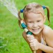 Happy girl pours water from a hose — Stockfoto