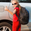 Happy girl standing near the car, ready to travel - Stock Photo